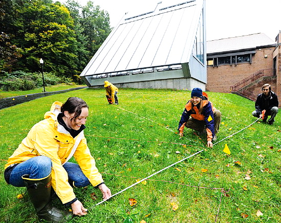 Greenfield Community College students Krystal Graybeal, Ian Walton, Karla Muise and Sebastiano Ratti Pistoi use tape measures to lay out gardens and paths for the permaculture gardens they are planting next to the new greenhouse at the south end of the GCC main building. (Recorder/Paul Franz)