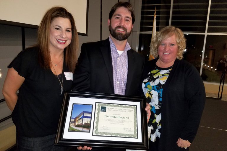 Chris Doyle, center, receives the 2016 Distinguished Alumni Award from Greenfield Community College Foundation board members